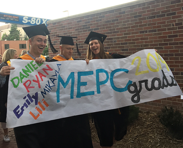 Three grad students in cap and gown walk to their 2019 commencement ceremony across campus holding an MEPC Grads banner