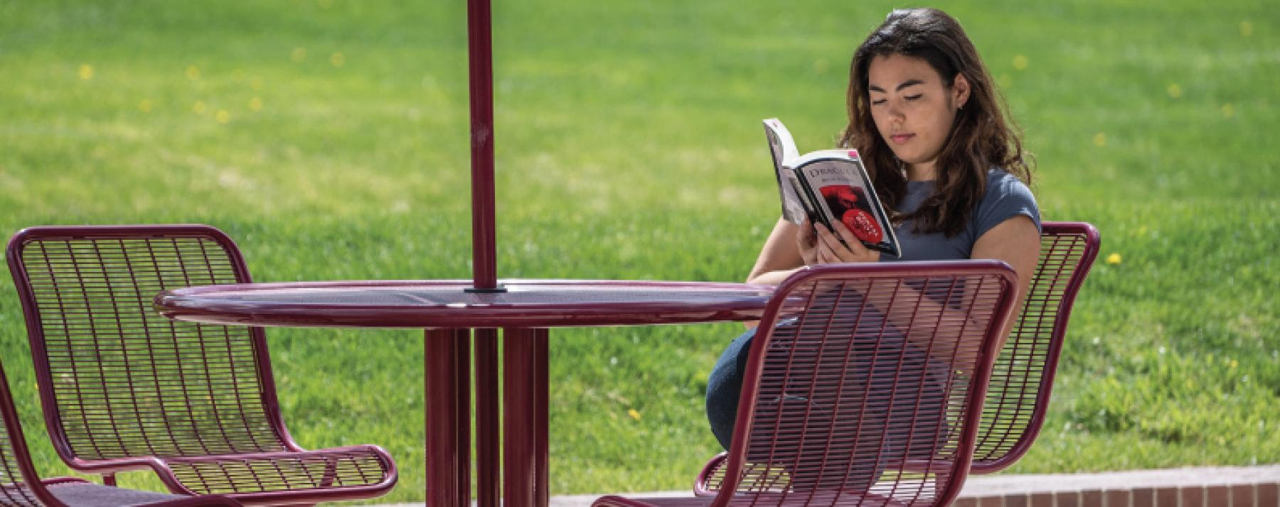 student reading outdoors on campus