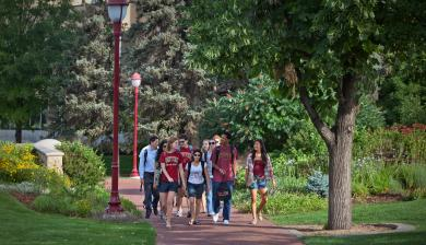 A group of students walks across campus behind the Mary Reed Building