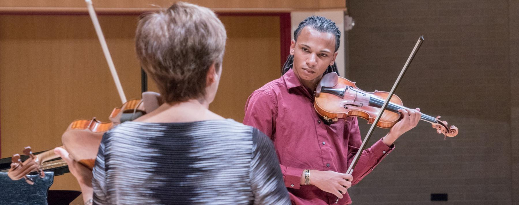violin student practicing with instructor